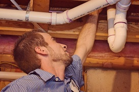 United Plumbing - Sewer-Line-Repair-Sewer-Gas-Springfield-Missouri-image of repairman working on sewer pipes in sub-floor or a house